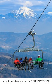 STARI VRH, SLOVENIA - FEBRUARY 8th 2018: Skiers driving on a ski lift to the Stari vrh ski track with Storžič mountain in the background on a sunny winter day.