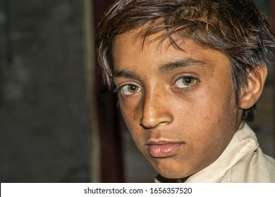 staring weak hungry child in inside a room