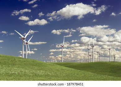 Stark white power generating wind turbines, under Spring blue sky, behind a field of green rangeland, California.