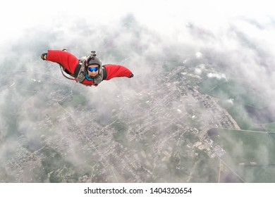 STARODUB/RUSSIA - May 18, 2019: Wingsuit skydiver with the action camera flying in the clouds.