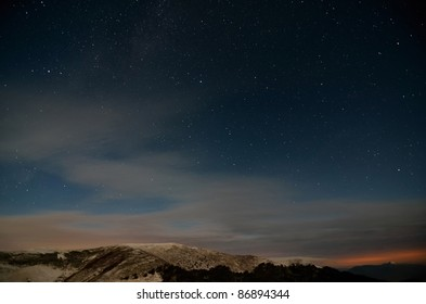 Starry cloudy sky in the mountains