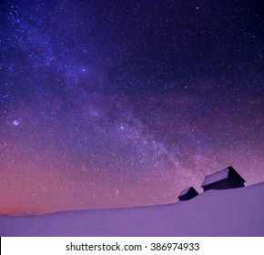 starry cloudy winter sky with milky way above abandoned huts