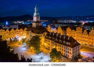 Starry evening over Jelenia Gora market square. Beautiful illuminated town hall building, old tenement houses and restaurants around central place. In a distance surrounding mountains - Shutterstock ID 1783402640
