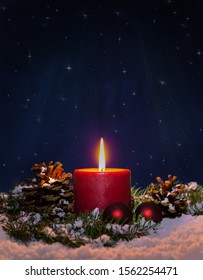 Starry holiday night with burning red candle on snow