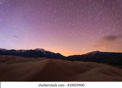 Starry Night at Great Sand Dunes - Star trails of spring night sky above snow peaks and sand dunes at Great Sand Dunes National Park & Preserve, Colorado, USA.