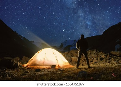 Starry night mountain landscape with glowing tent and looking at the sky person.