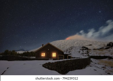 starry night on Galvarina Refuge with windows glowing under snowy Etna Volcano, Sicily