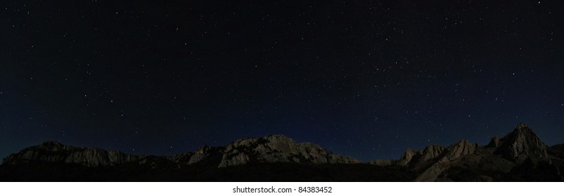 Starry night sky above rocky cliffs. Natural stars panorama photo