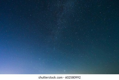 Starry night sky with Milky way and a glimpse of Northern lights.
