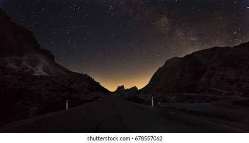 Starry night sky with the Milky Way over a mountain road. Italian alpes