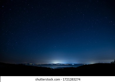Starry night sky over city lights.  - Shutterstock ID 1721283274