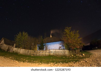 Starry night in the village of Mezmay and a house with a stove behind a wooden fence
