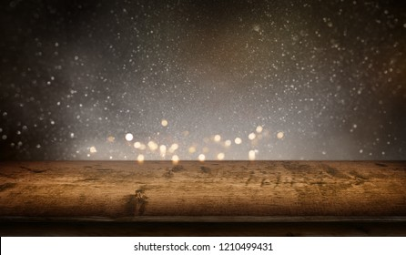 Starry sky with gold bokeh and rustic wooden table for a christmas decoration