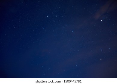 Starry sky with little clouds. Bright colored stars over us on the dark blue sky background.