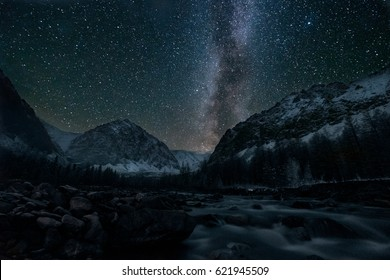 Starry sky with Milky Way above house river and mountain peak
