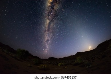 Starry sky and Milky Way arc, outstandingly bright, with rising moon, captured from the Namib desert in Namibia, Africa. The Small Magellanic Cloud on the left hand side.