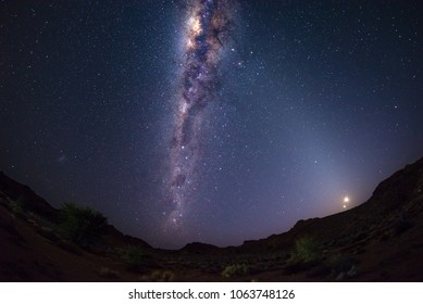 Starry sky and Milky Way arch with moon in the Namib desert in Namibia, Africa. The Small Magellanic Cloud on the left hand side.
