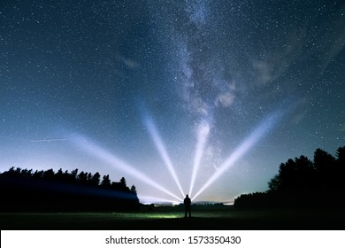 Starry sky and milky way. Man with flashlight in the foreground