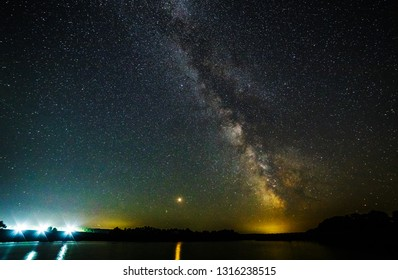 Starry sky and the milky way over the water.Bright star Mars.