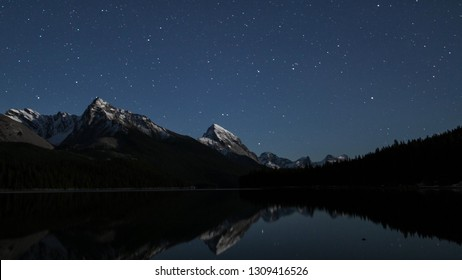 A starry sky over Canadian Rockies reflecting in a still lake in Jasper National Park, Alberta. Astrophotography.