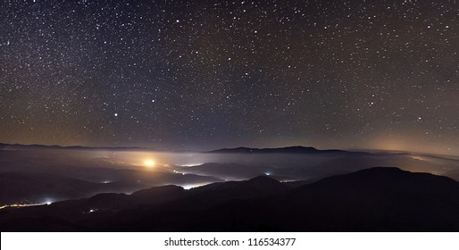 Starry sky over foggy mountains panorama with city lights below