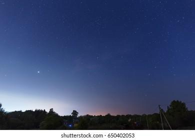 Starry sky over the small dark village