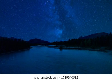 Starry Sky Reflected in River Over Mountain Wilderness Landscape