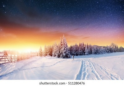 Starry sky at snowy night and road in the mountains. Fantastic milky way in the New Year's Eve