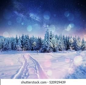 starry sky in winter snowy night. fantastic milky way in the New Year's Eve. Winter road in the mountains. Bokeh light effect, soft filter. Photo greeting card