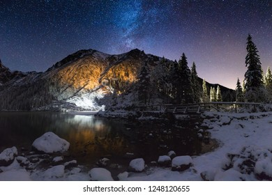 Starry winter night in mountains. Milky way over mountain peak in deep blue night sky. Colorful night landscape with snow and mountains.