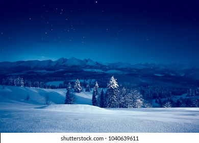 Starry winter night. Stunning night landscape. Sky full of stars over snowy mountains and valley.