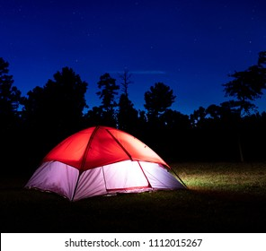 Stars above a lighted nylon tent pitched in North Carolina