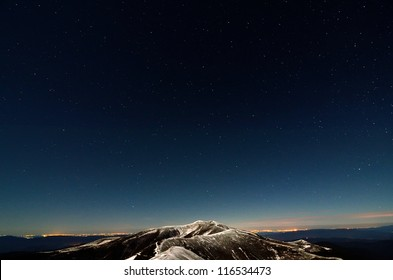 Stars above snowy autumn mountain ridges and city lights