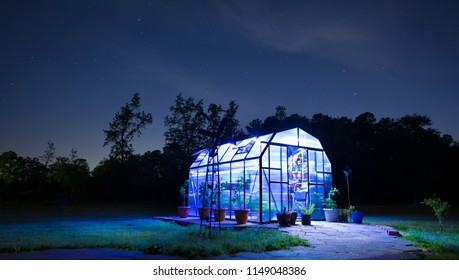 Stars and clouds in the sky with a lighted greenhouse underneath