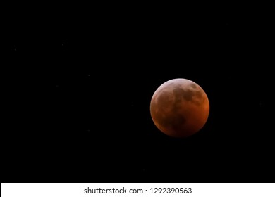 Stars light the night sky as the moon is covered with the earth's shadow during a total lunar eclipse.