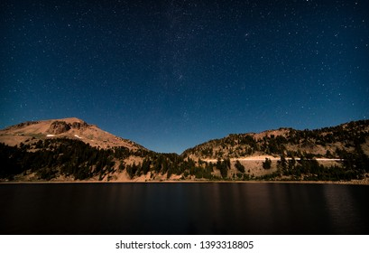 Stars in the Milky Way Galaxy, and light trails from a highway, over a lake at Lassen Volcanic National Park in Northern California