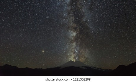Stars of the Milky Way at night in the sky above Mount Elbrus. View of the northern slope of the two peaks of the stratovolcano. The highest peak of Russia and Europe is 5642m.