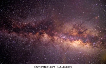 The stars and the Milky Way shine in the dark sky.