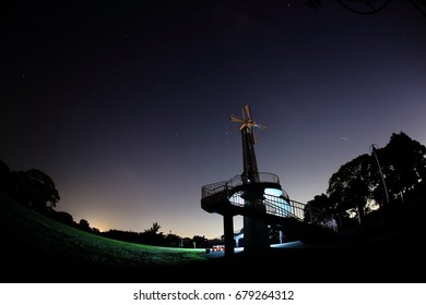 Stars in the night sky and metallic windmill. Shot with fish-eye lens