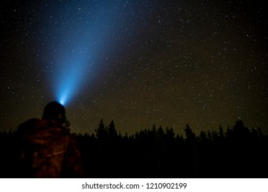 Stars in the Night Sky with the silhouette of trees and a Person with a Head lamp