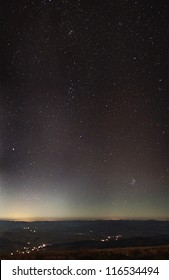 Stars over city lights and cloudy mountains panorama under moonlight