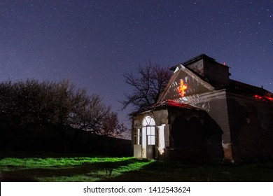 Stars over an old abandoned rural church. White ligthing inside abandonded church.
