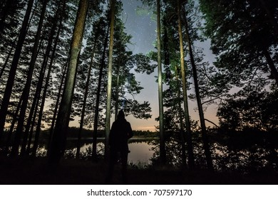 Stars over the trees at summer night on dark sky. Starfall. Milky way. Pine trees. Man standing with torch light mounted on the head.