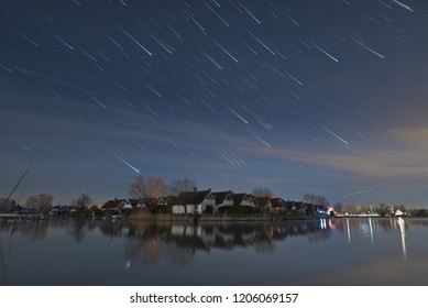 Stars seem to fall down and form star trails with meteor effect, created as the earth rotates, in Seepark Weiden at Lake Neusiedlersee in Austria at night.
