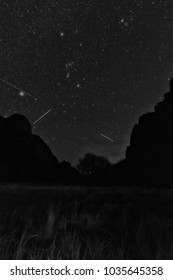 Stars shine in the night sky above red cliffs in Zions national park.