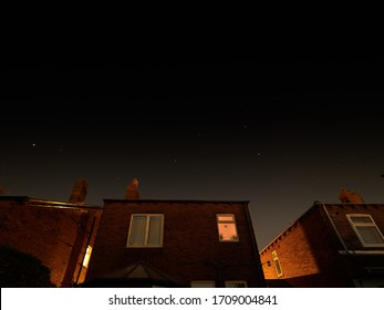 Stars sparkle clearly on a cloudless night over houses on a street in Wakefield, Yorkshire.