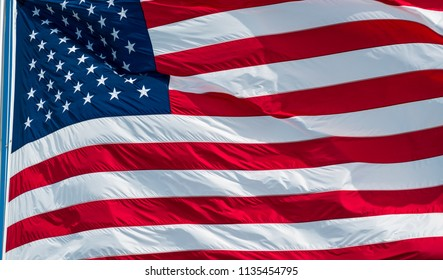 Stars and Stripes on a large symbol of the United States of America . Perfect huge American flag waving in the sunshine on a nice blue sky sunny windy day