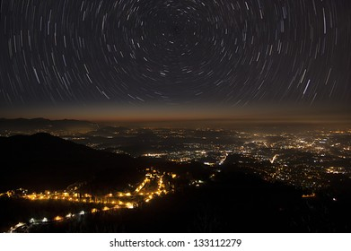 stars trails over the horizon and city