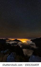 Starscape above the Caldera de Taburiente in La Palma, Spain with illuminated villages below the clouds.