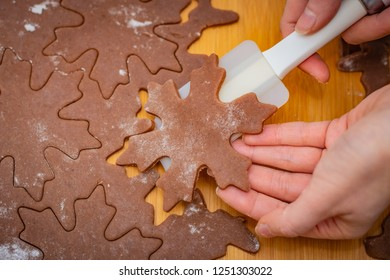 Star-shaped cake is lifted by a woman's hands with a white spatula, the preparation for Christmas pastries